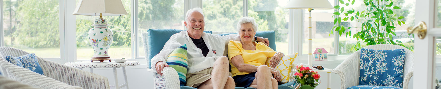 An elderly couple sitting in the living room area of their independent living villa at Village on the Green