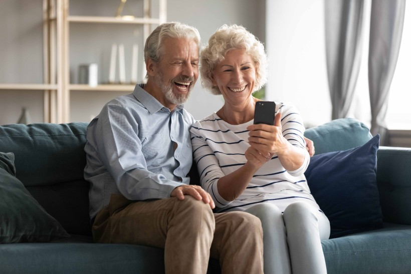 two seniors video chatting their family on their smart phone