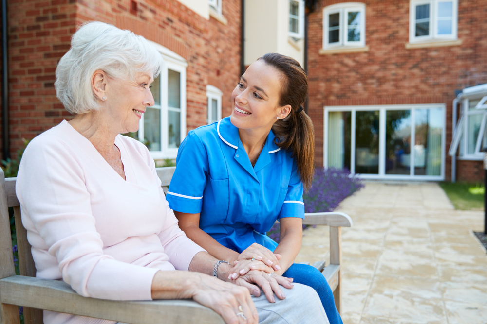 Senior woman sitting on a bench with a nurse