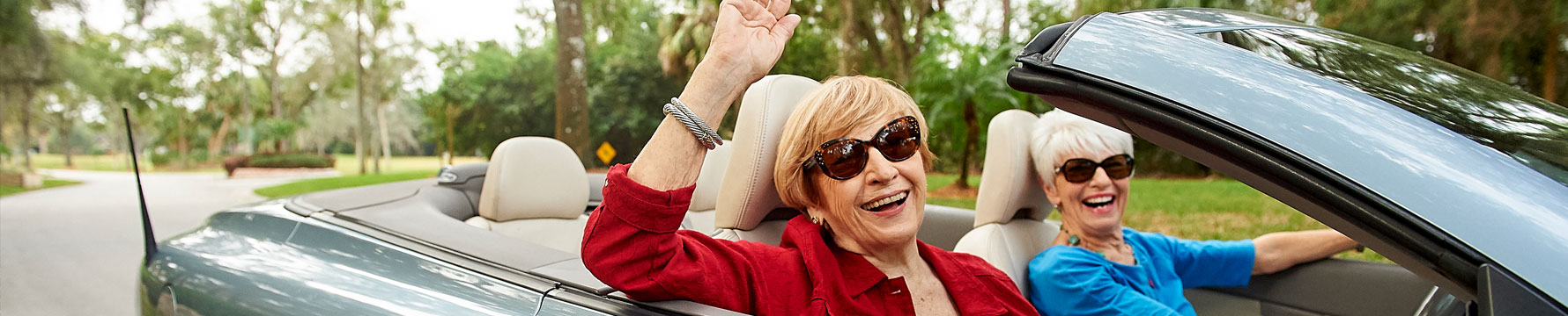 Two senior ladies riding around in a silver convertible with the top down