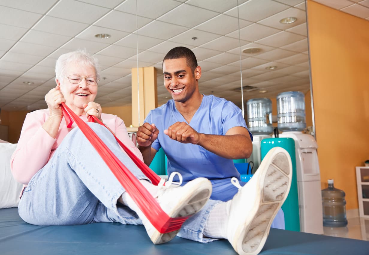 Older woman stretching with a band next to her therapist.