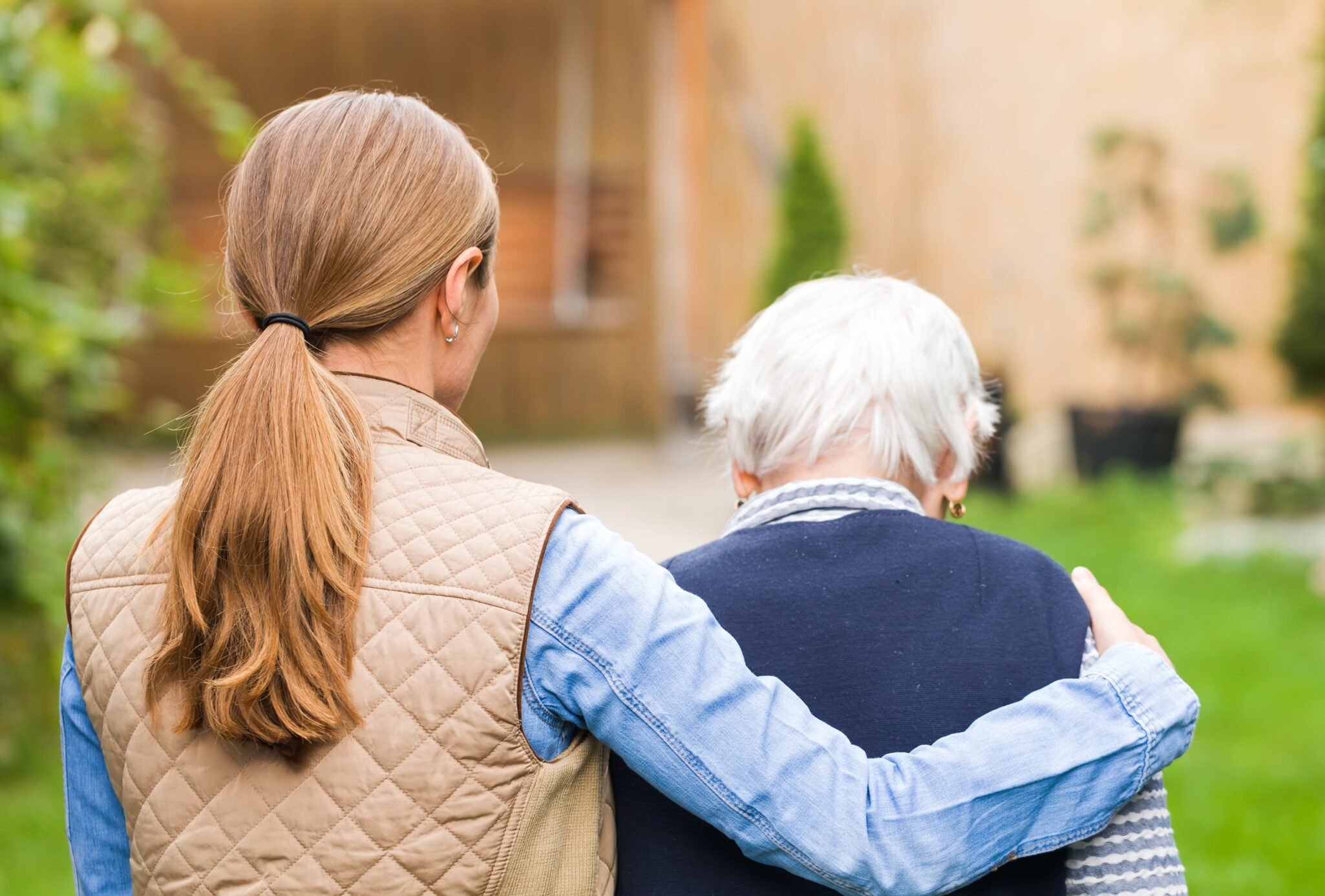 Female caretaker with arm around senior woman with dementia.