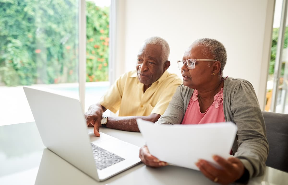 Senior couple planning for retirement sitting in front of laptop at table.
