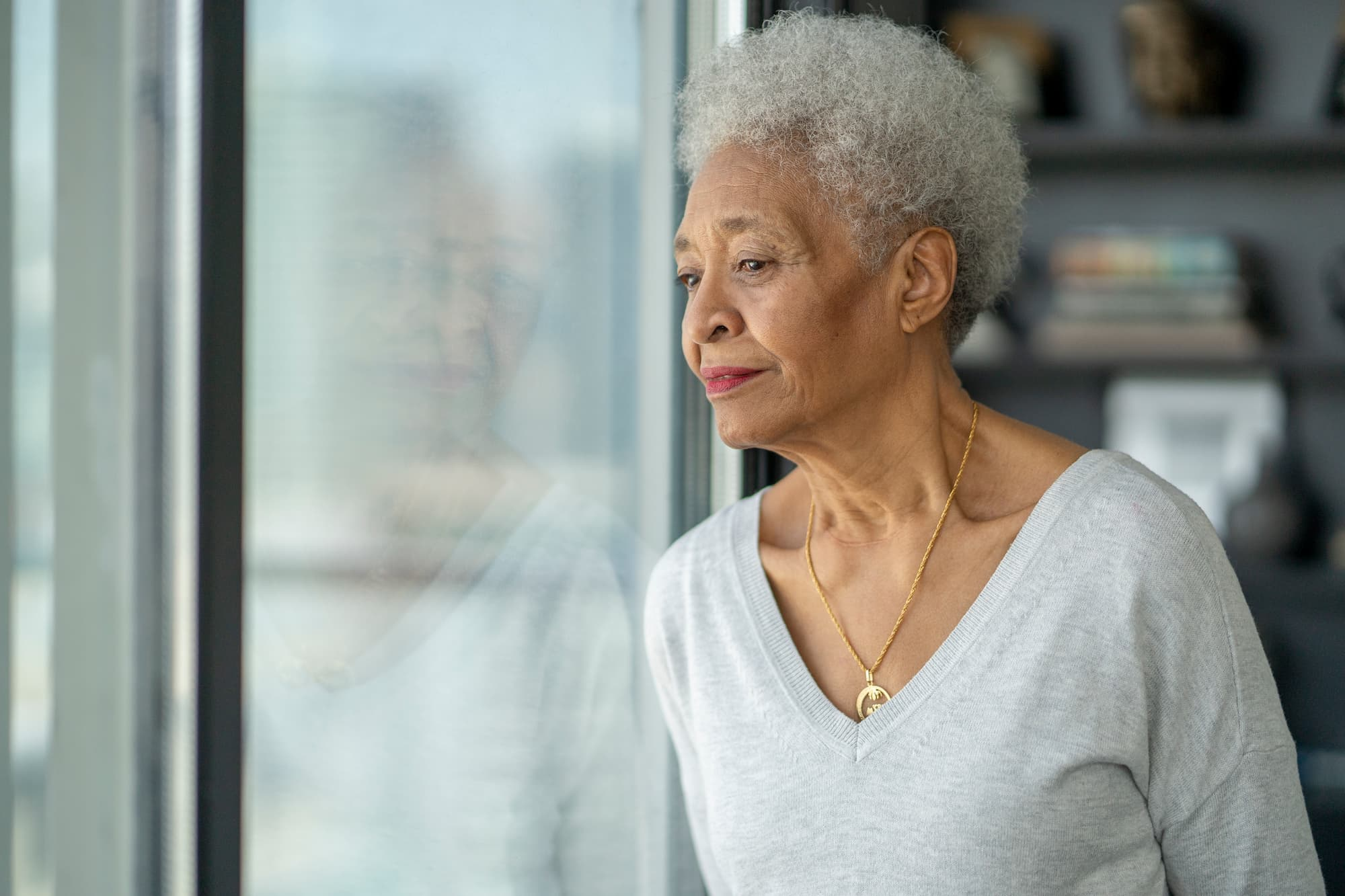 Older woman looking out a window, in thought.